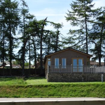 View of holiday home with decking and stone wall